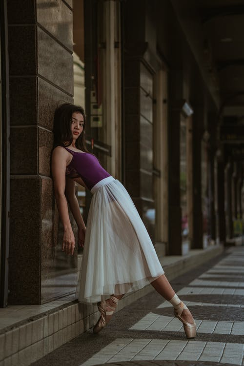 Woman In Purple Tank Top And White Skirt