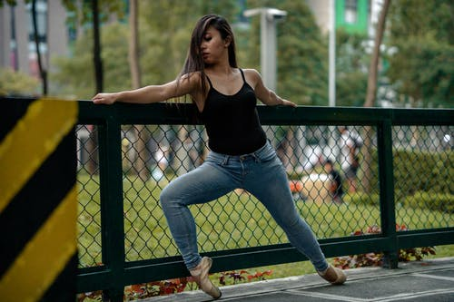 Woman In Black Tank Top And Blue Denim Jeans Holding On A Fence