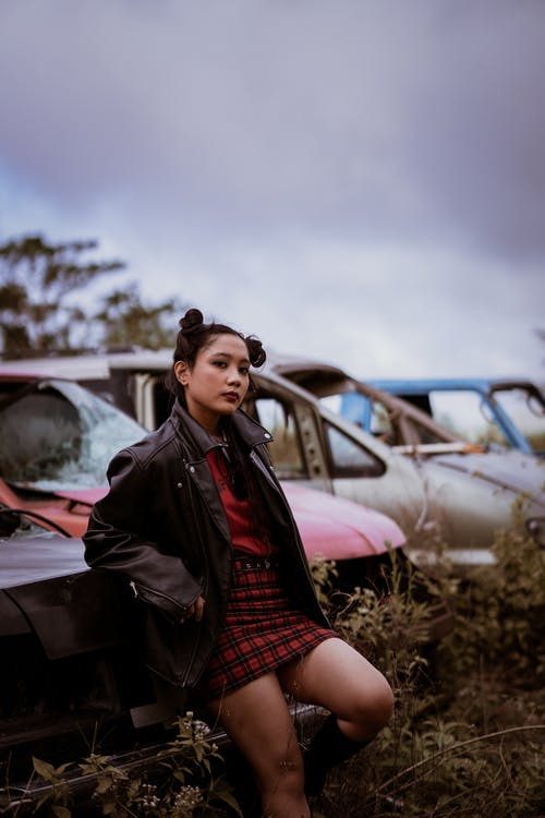 Woman in Black Leather Jacket and Red and Black Plaid Dress Shirt Sitting on Brown Grass
