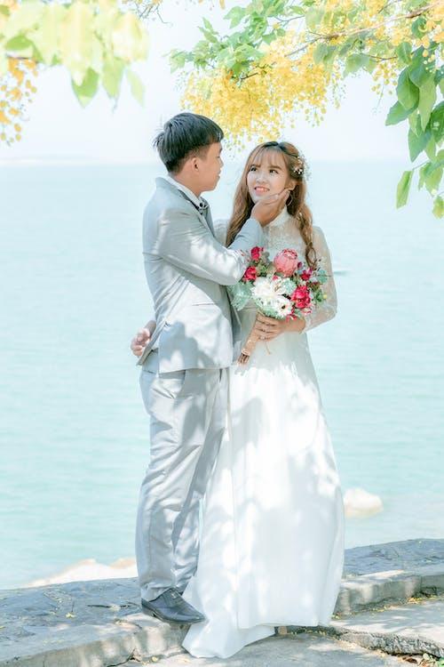 Newlywed couple near lake on sunny day