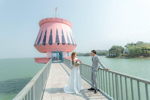 Stylish newlywed couple standing on bridge