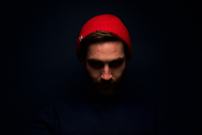 Man Wearing Red Knit Cap in Dark Room