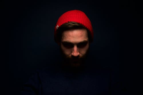 Man Wearing Red Knit Cap in Dark Room