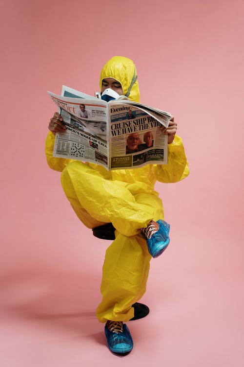 Man In Yellow Protective Suit Holding A Newspaper