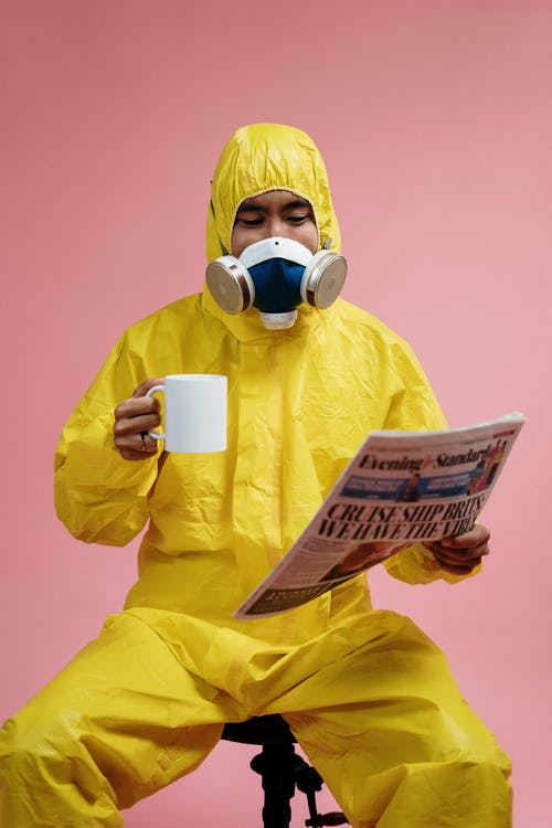 Person In Yellow Protective Suit Reading The Newspaper