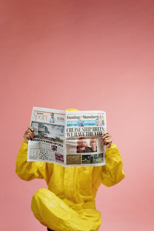 Person in Yellow Coveralls Reading Newspaper