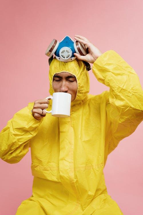 Man in Yellow Coveralls Holding Ceramic Mug