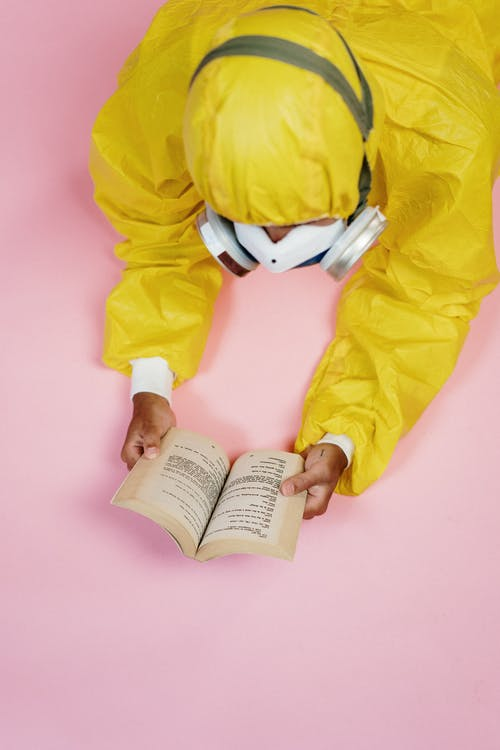 Person In Yellow Protective Suit Reading A Book