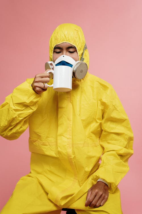 Person In Yellow Protective Suit Drinking