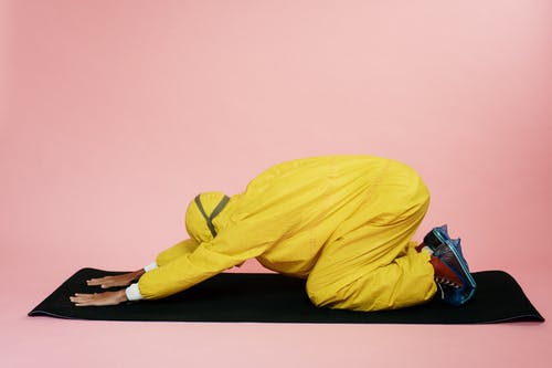 Person In Yellow Protective Suit Doing A Yoga Pose