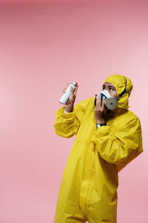 Man in Yellow Coveralls Holding Spray Bottle