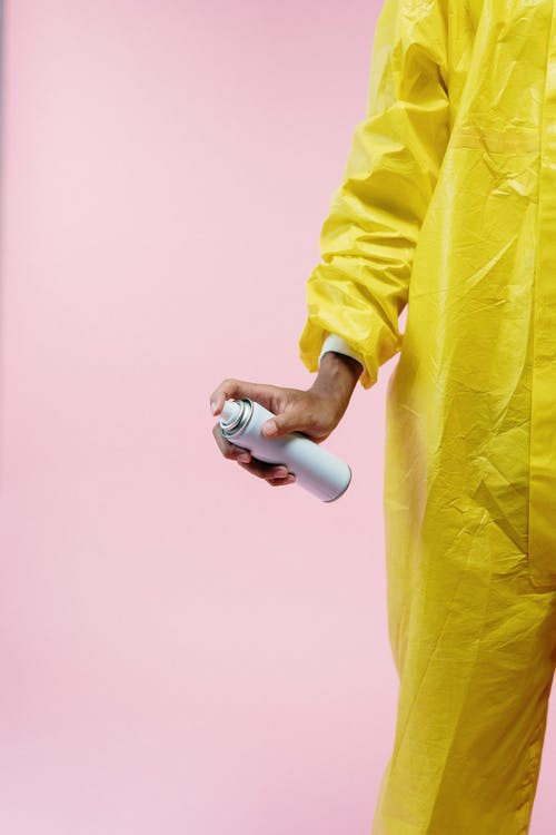 Person In Yellow Protective Suit Holding Aerosol Can