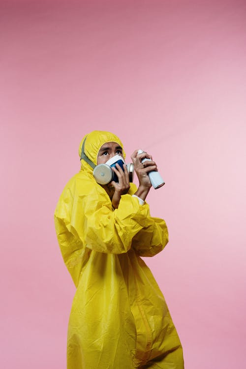 Person in Yellow Coveralls Holding Spray Bottle