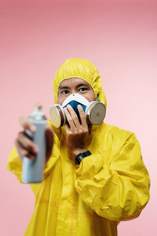Man in Coveralls Holding Spray Bottle