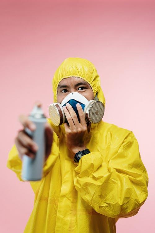 Man in Coveralls Holding Spray Bottle