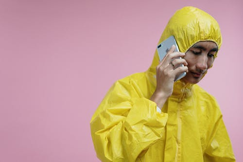 Man in Yellow Coveralls Talking on Phone