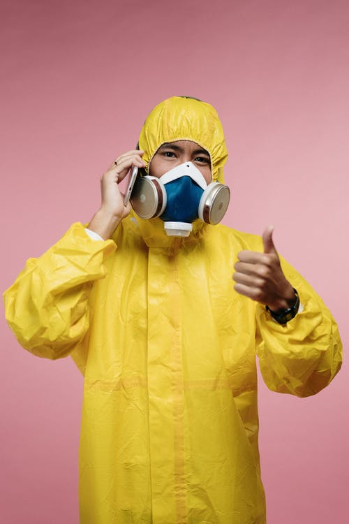Person In Yellow Protective Suit Talking On The Phone
