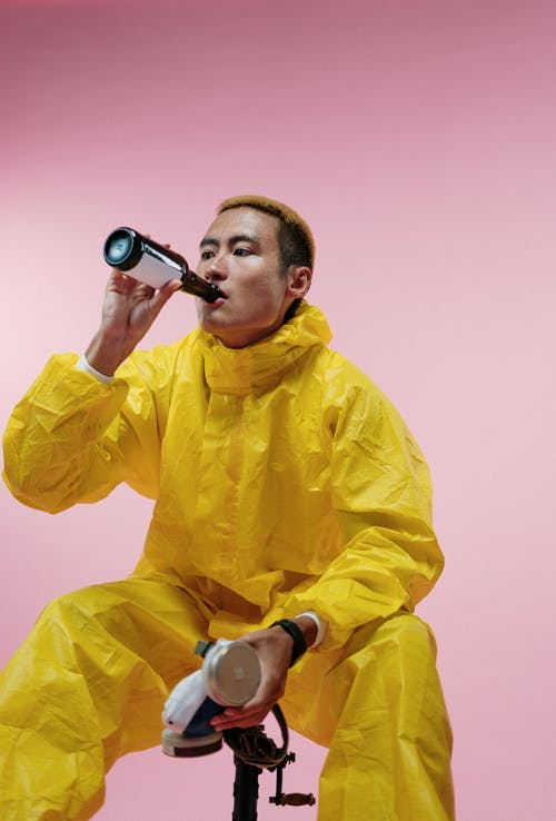 Man in Yellow Coveralls Drinking Beer