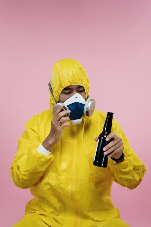 Person in Yellow Coveralls Holding Beer Bottle