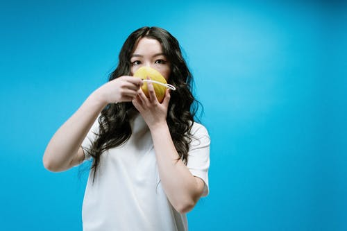 Woman in White Shirt Holding Yellow Fruit