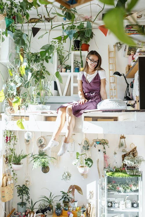 Young woman sitting in apartment on second level with plants
