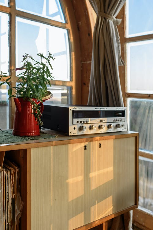 Vintage stereo radio set on music cabinet in wooden room with windows and plant in daytime nobody at home corner of room