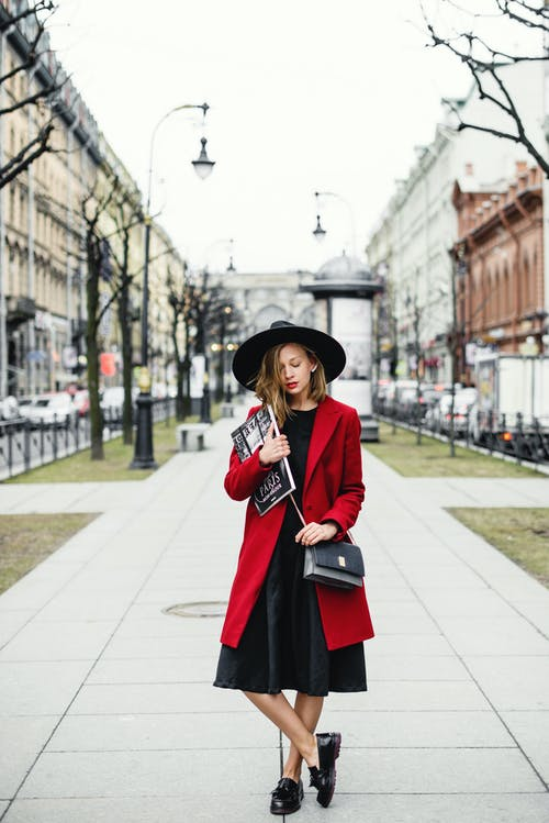 Woman in Black Hat and Red Dress Standing on Sidewalk