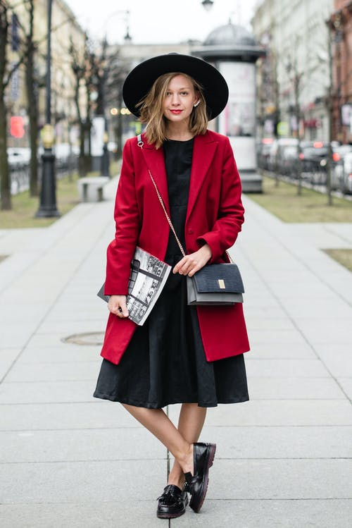 Woman in Red Coat and Black Dress Holding Book
