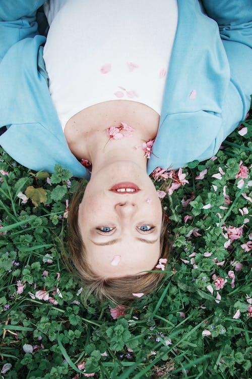 Woman in Blue Shirt Lying on Green Grass