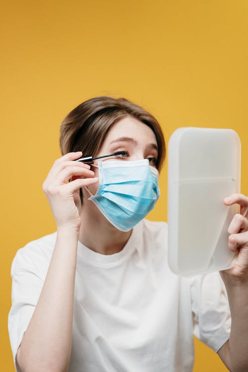 Woman in White Crew Neck T-shirt Covering Her Face With Face Mask