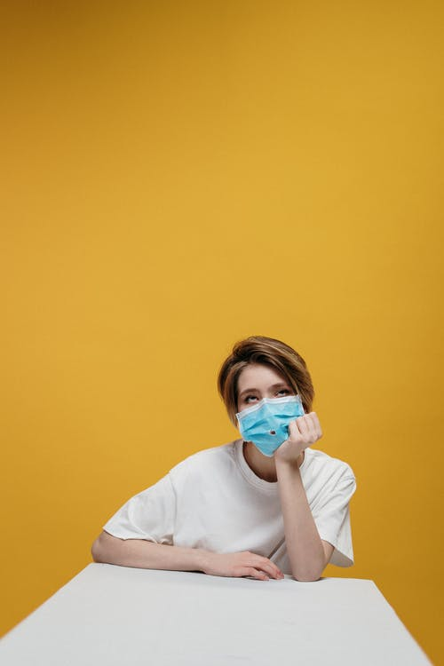 Woman in White Crew Neck T-shirt Wearing Face Mask