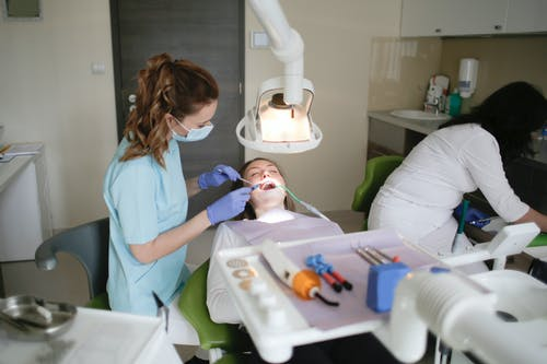 Woman In Blue Scrub Suit Checking A Patient's Teeth