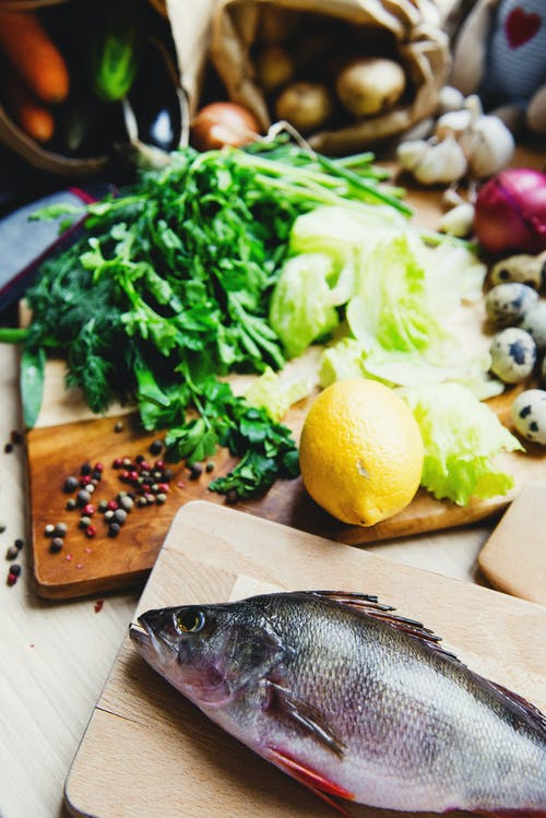 From above of whole raw fish and fresh vegetables with black pepper grains put on wooden cutting boards in sunlight at home