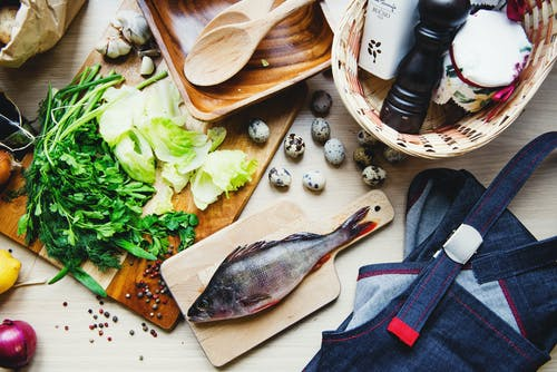 Top view of fresh fish and vegetables put on cutting board near wooden dishware and wicker basket with pepper shaker and jar in kitchen