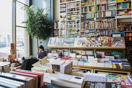 Female customer using social media on smartphone sitting in bookstore