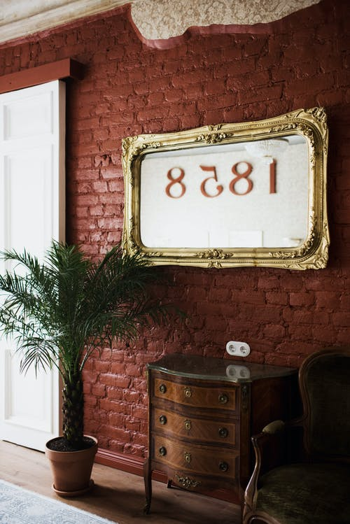 Golden frame with numbers on brick wall