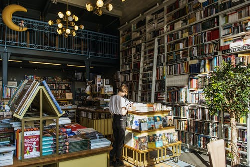Person In White T-shirt Standing Beside Books Inside A Library