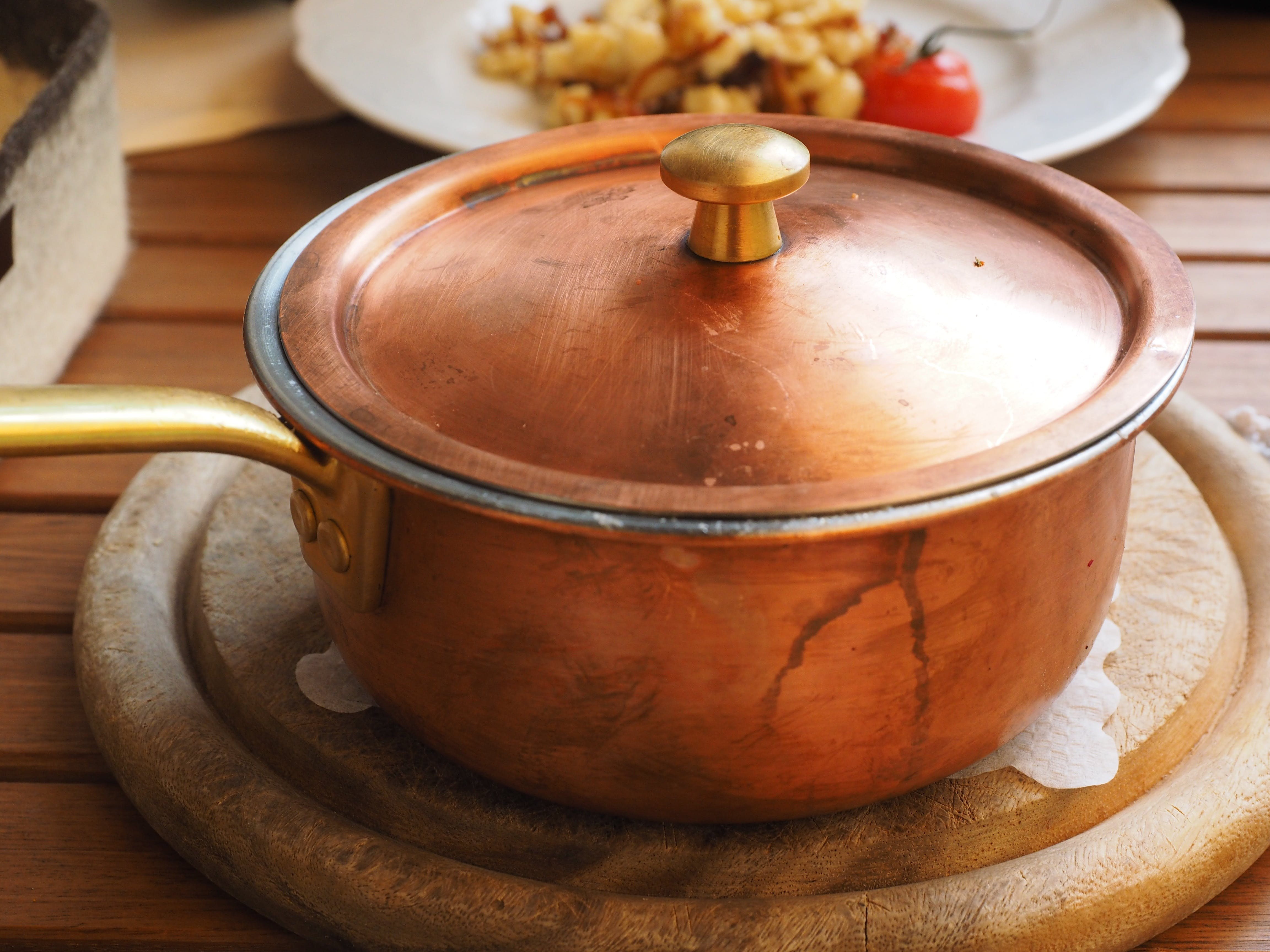 Brown Lidded Cooking Pot on Gray Round Wooden Coaster