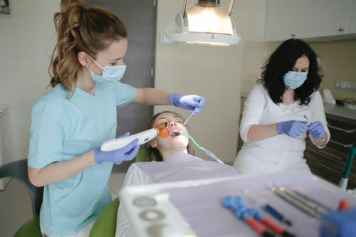 Woman in Light Blue Scrub Suit Holding Dental Curing Light