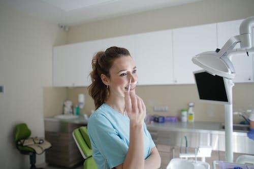 Smiling female dentist in uniform standing with dental tweezers