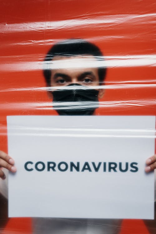 Man With Face Mask Holding A Poster With Coronavirus Text