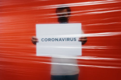 Man Behind A Plastic Holding A Poster Of Coronavirus