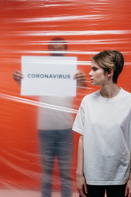 Woman With A Stressful Look At A Man Holding A Poster With Coronavirus Text