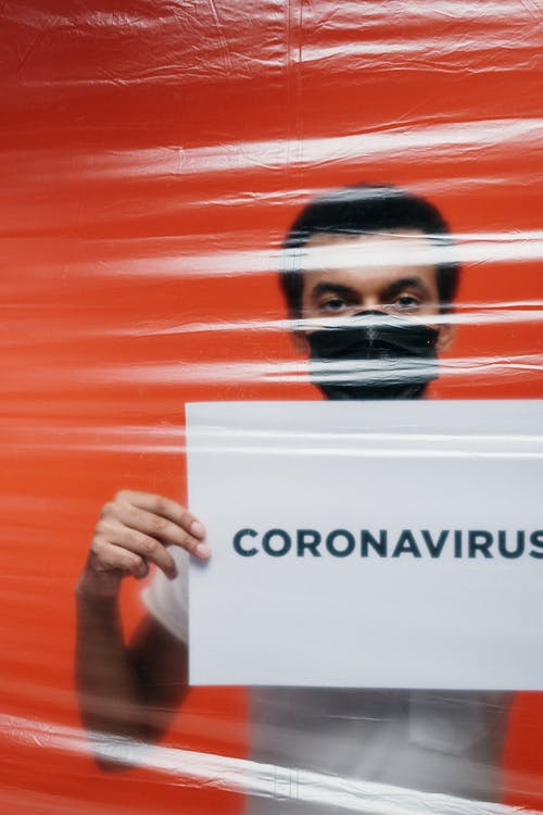 Man Behind A Plastic Holding A Poster With Concept Of Coronavirus