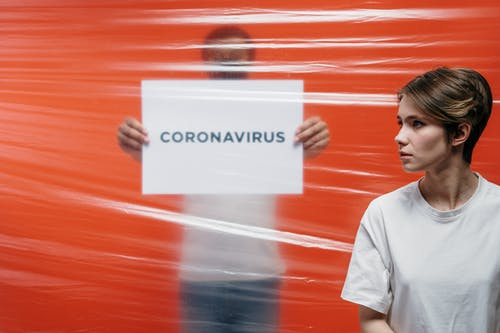 Man in White Shirt Holding A Sign Of Coronavirus