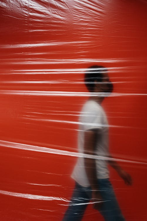 Man Walking In A Room Behind A Plastic
