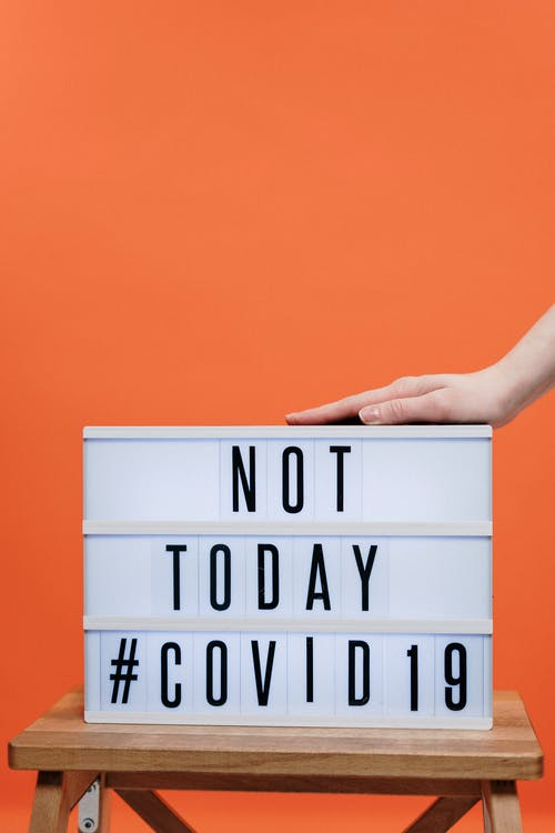 Person's Hand On A Covid19 Sign