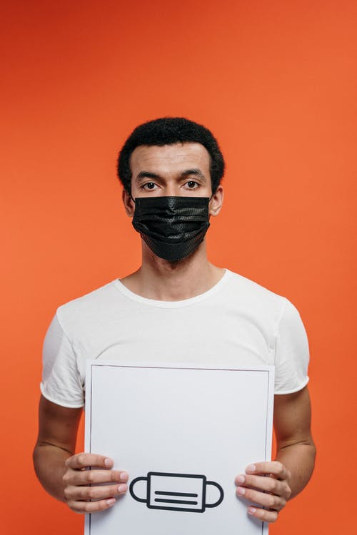 Man in White Crew Neck T-shirt Wearing Black Face Mask