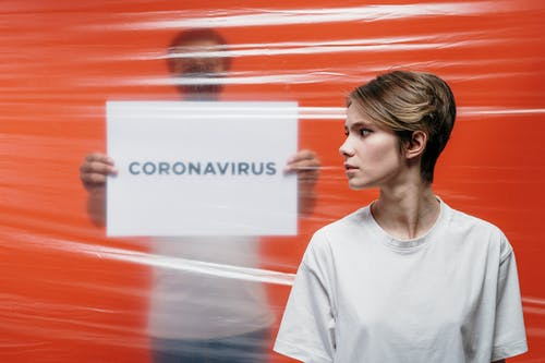 Woman in White Crew Neck T-shirt Standing Beside A Man Holding A Placard Of Coronavirus