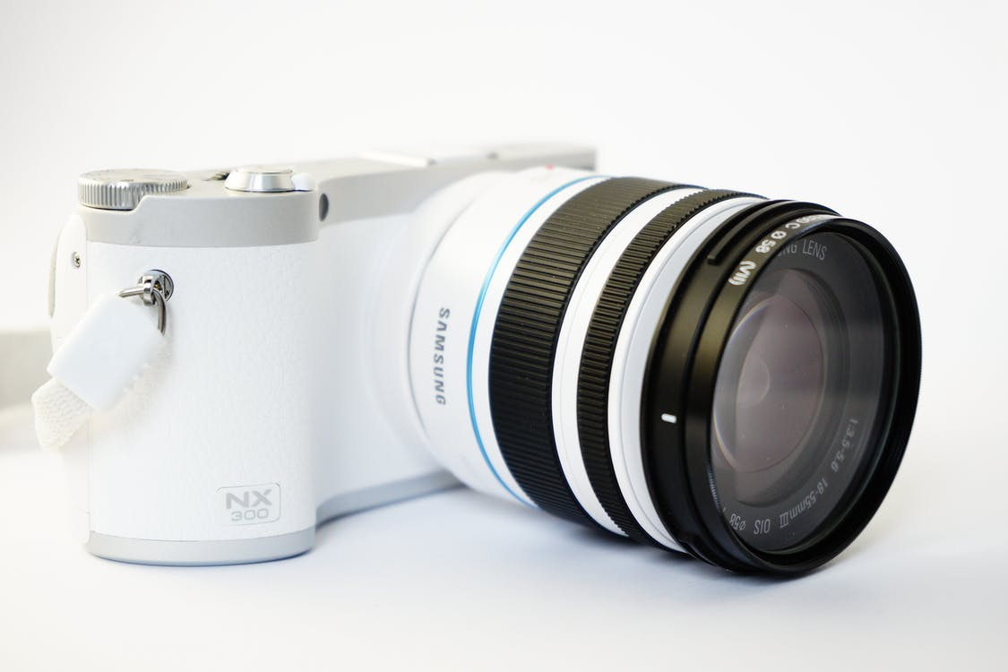 White and Black Samsung Nx 300 Dslr Camera on White Surface